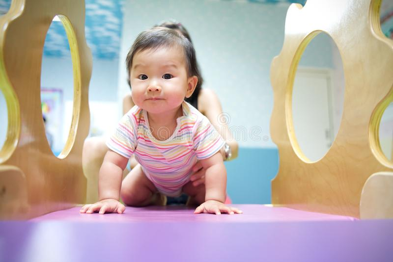 Young little smiling Asian baby enjoy playing in kid playground. Mother holding baby from her back to play on slider with stock images