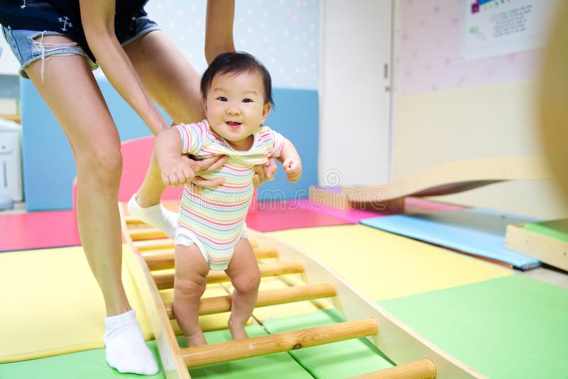 Young little smiling Asian baby enjoy playing in kid playground. stock photo