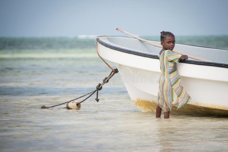 Young local kid playing by the fishing boat at Kiwengwa village, Zanzibar. KIWENGWA, ZANZIBAR - DEC 27, 2017: Young local kid playing by the fishing boat at royalty free stock images