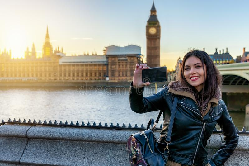 London traveler woman takes selfie pictures at Westminster, UK. Young London traveler woman takes selfie pictures with her phone at Westminster with view to the stock photos