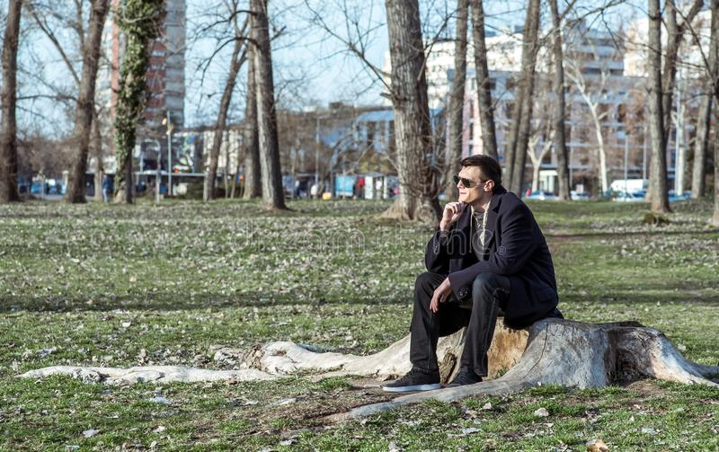 Young lonely depressed and anxious man sitting alone in the park on the wooden stump disappointed in his life crying and thinking stock photography