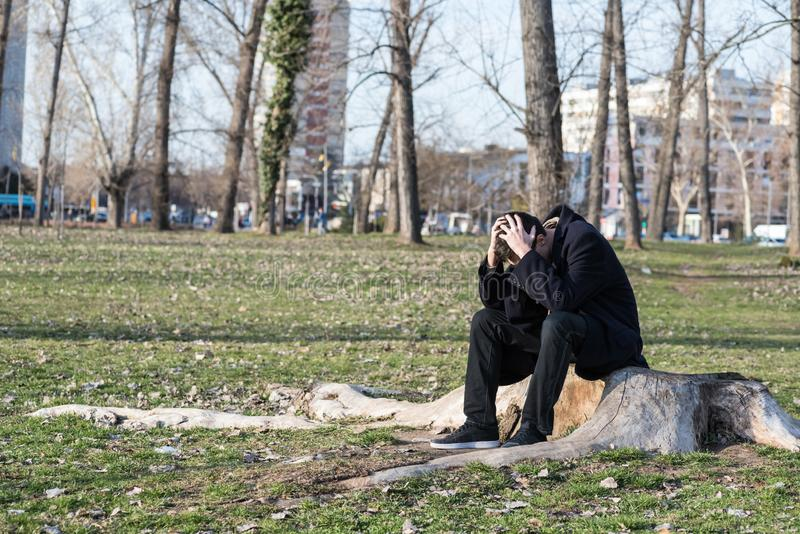 Young lonely depressed and anxious man sitting alone in the park on the wooden stump disappointed in his life crying and thinking royalty free stock images