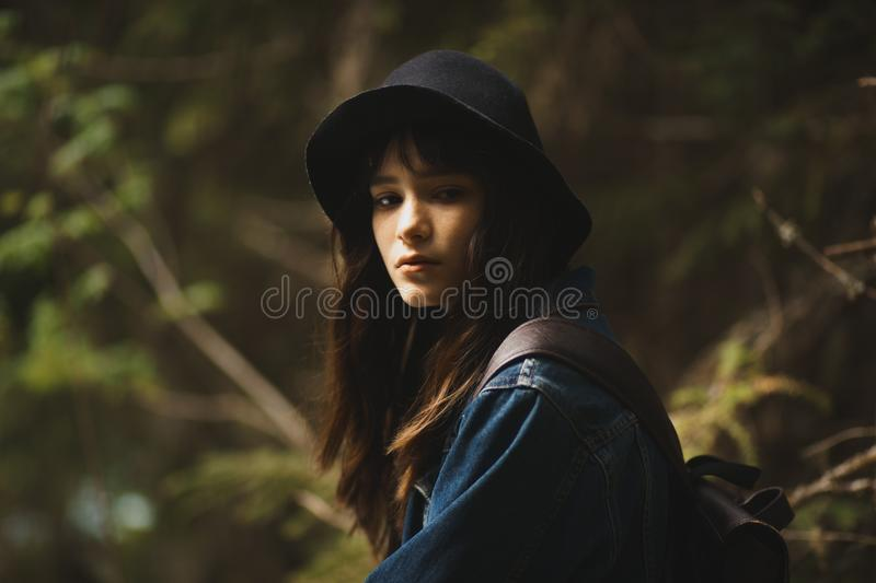 Young lonely tourist cutie girl sitting on stone on shore of river in mountains in wild terrain and satisfying thirst stock photo