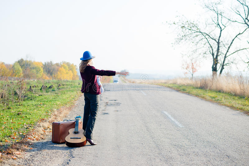 Young lonely woman and baby hitchhiking on rural. Hitchhiking pretty young lonely lady holding baby on rural roadside with suitcase and guitar on sunny day in royalty free stock images