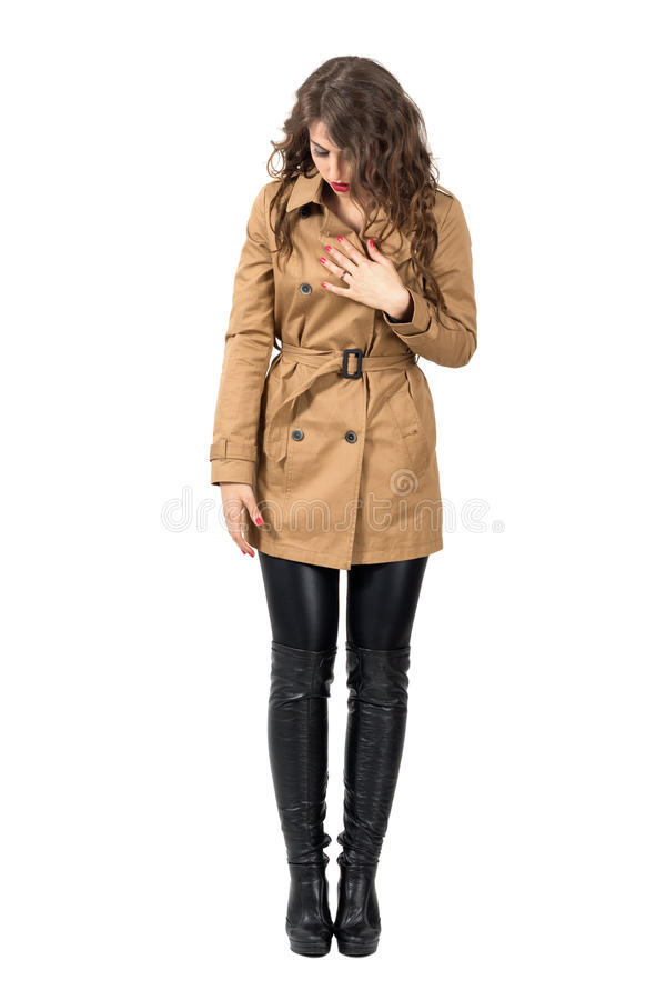 Young long hair woman holding beige coat looking down. stock photo