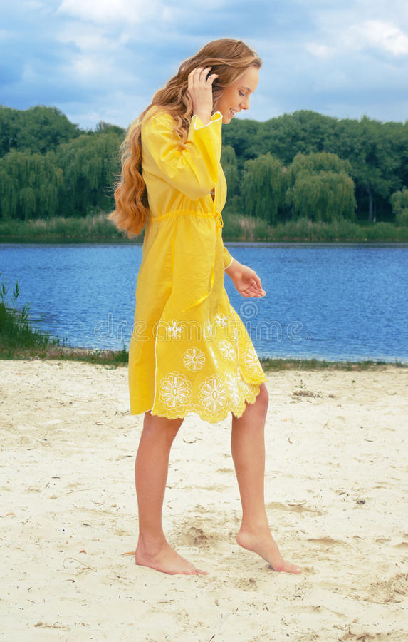 Young long-haired attractive woman in yellow outfi royalty free stock photo