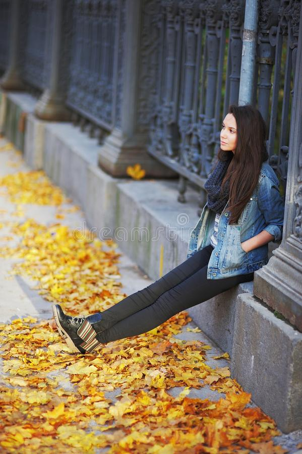 Young long-haired brunette sitting on a concrete curb around the cast-iron fence, under the feet of yellow autumn maple royalty free stock photos