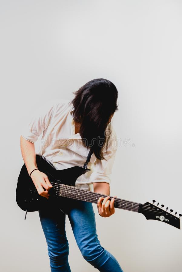 Young long haired guitarist excited playing his black electric guitar, isolated on white background royalty free stock photo