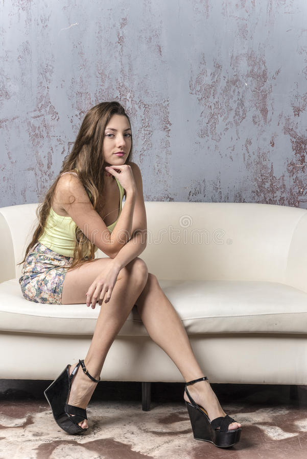 Young long-haired long-legged skinny girl in a top mini skirt and platform sandals. Smiling stock photos