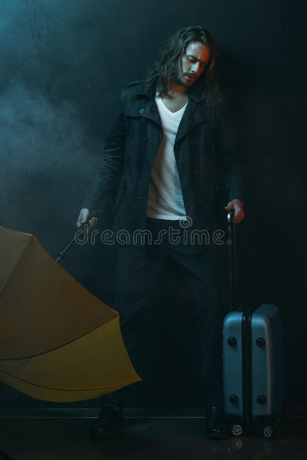 Young long haired man holding yellow umbrella and suitcase stock images