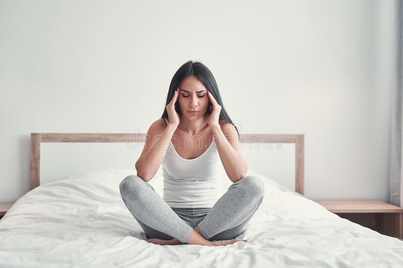 Young Girl Sitting On Bed Crossing Legs Closeup High-Res