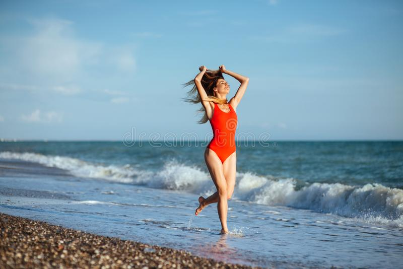 Young longhaired girl in red swimsuit royalty free stock photo