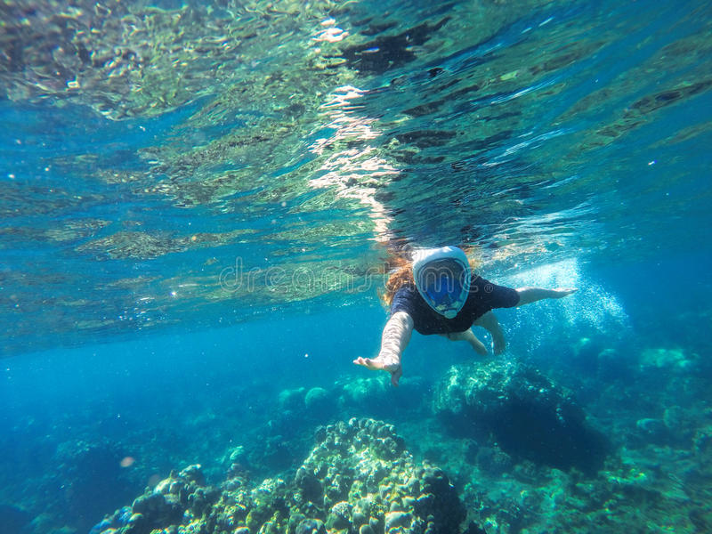 Young loose hair woman snorkeling in blue mask in coral reef stock photos
