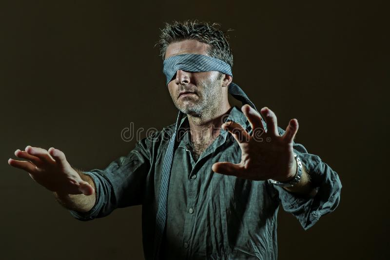 Young lost and confused man blindfolded with necktie playing internet trend dangerous viral challenge with eyes blind isolated on. Young lost and confused man stock photos