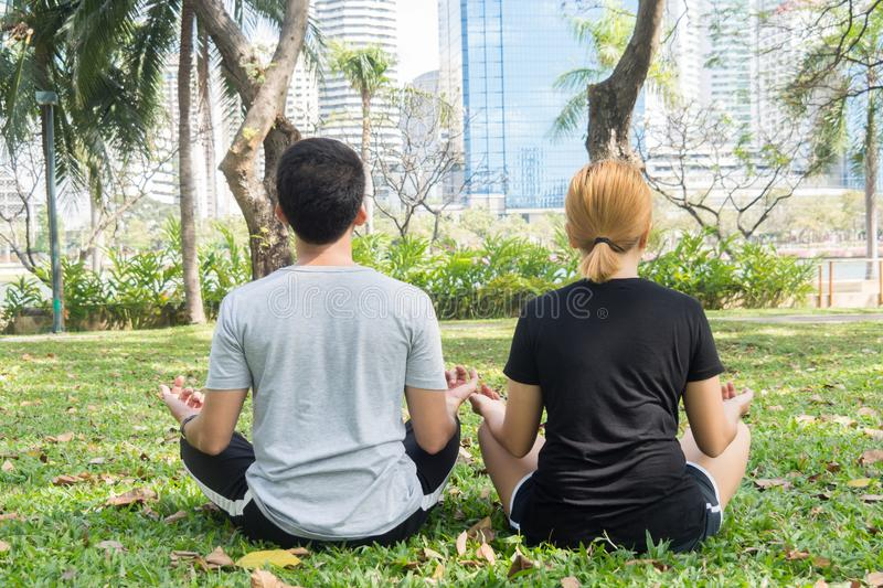 Young love couple making a meditation to calm their mind after exercising in park encircle with a warm light sunshine. royalty free stock images