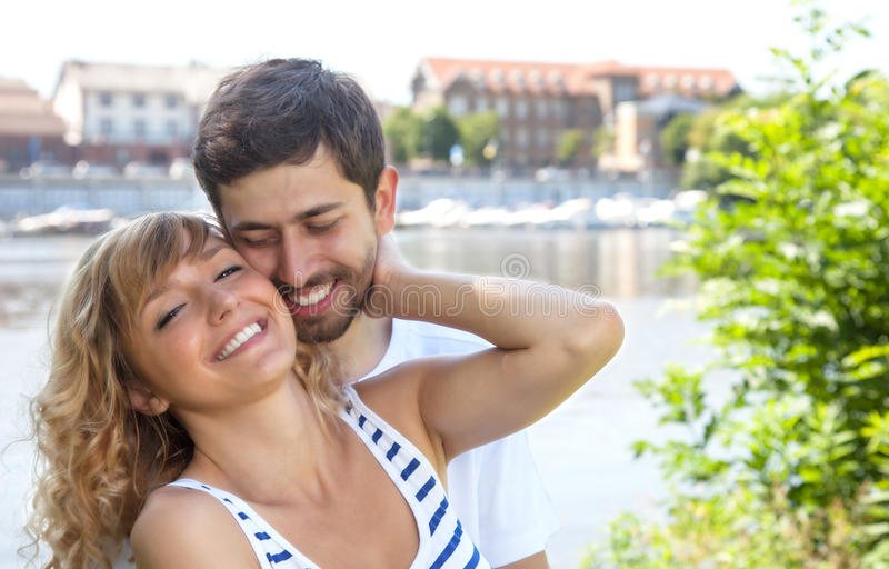 Young love couple on a marina. With water and city at the background on a sunny summer day stock image