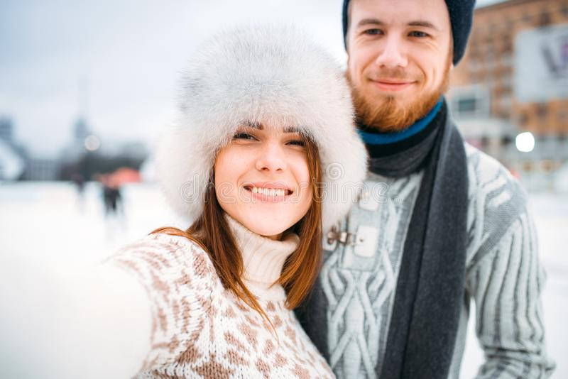 Young love couple, selfie on skating rink. Winter ice-skating on open air, active leisure, men and women skates together royalty free stock images