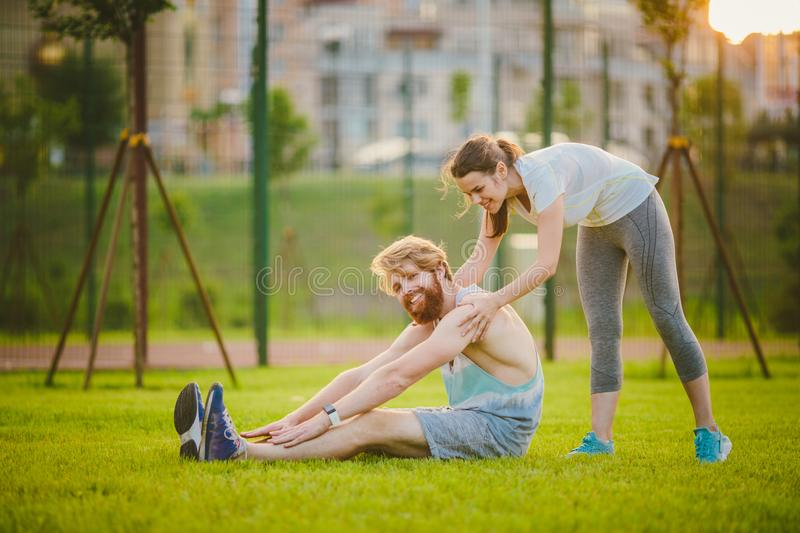Young in love heterosexual Caucasian couple, man with beard woman with big breasts doing exercise stretching muscles royalty free stock photography