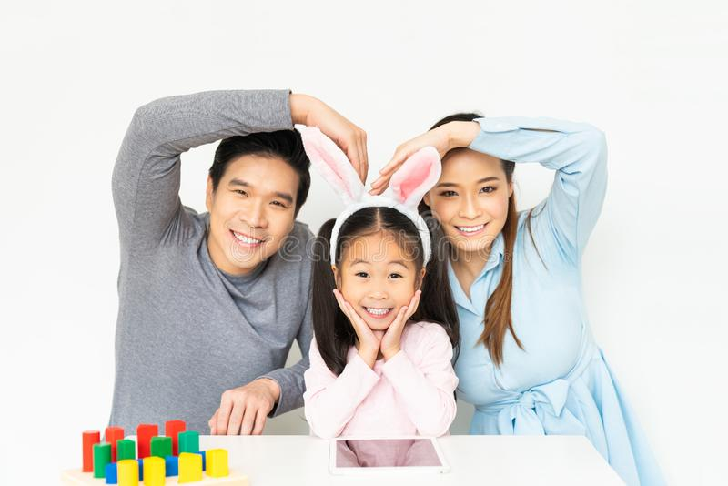 Young lovely Asian family, parents and small kid girl doing funny pose and smiling together at home. Happy family love concept stock image