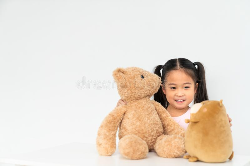 Young lovely Asian girl playing with 2 cute teddybear dolls at home, copy space on white wall background stock photo