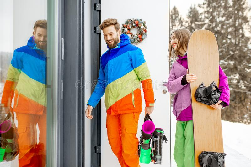 Couple in ski suits coming home in the mountains. Young lovely couple in coloful ski suits entering home or hotel after snowboarding in the snowy mountains stock photos