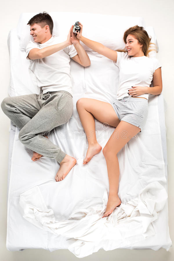 The young lovely couple lying in a bed with alarm clock. The young lovely couple lying in a white bed with alarm clock, love lconcept, top view royalty free stock images