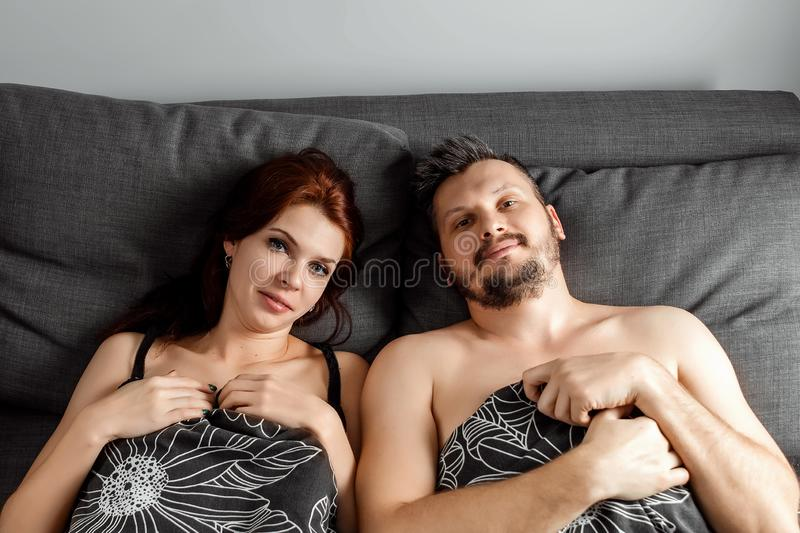 Young lovely couple lying in a bed, happy smile love looking to each other, top above view, hold hands heart shape stock photos