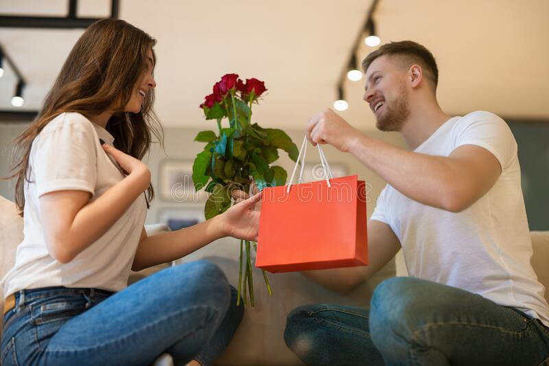 Young lovely couple sitting on the sofa, man surprising wife with roses and gift on saint valentine`s day, happy romantic stock photos