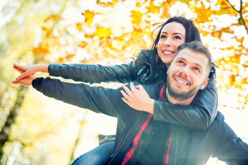 Young lovely happy couple - lovers flying in autumn park.  stock photography
