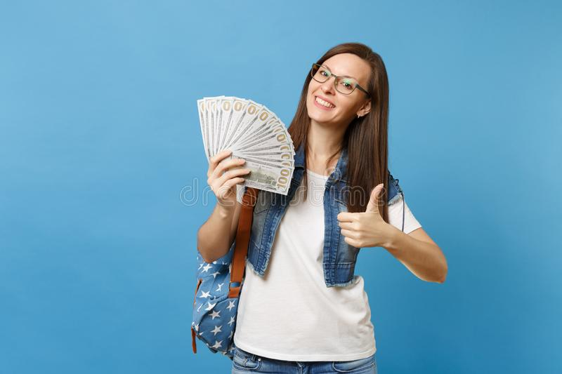 Young lovely happy woman student in glasses with backpack showing thumb up holding bundle lots of dollars, cash money. Isolated on blue background. Education in stock photography