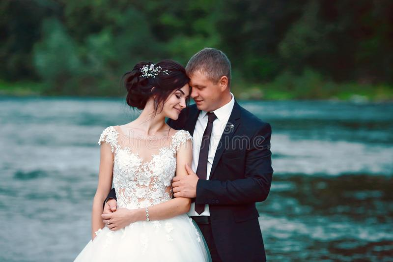 Young lovers are happy to walk in nature near river. Wedding day for man and woman royalty free stock photo