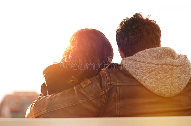 Young lovers at sunset. Closeup rearview of men embracing his women while sitting on bench. They are sitting outdoor and looking away in a beautiful sunset light stock image