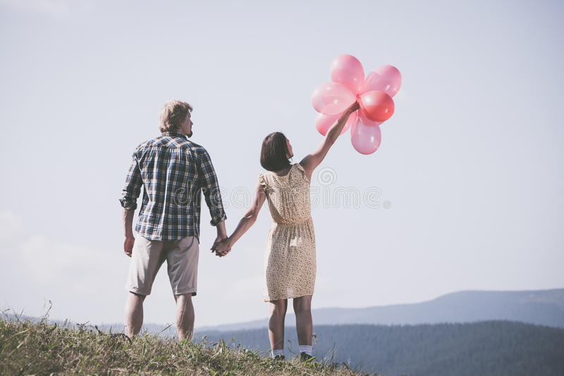 Young loving couple with balloons. On sky background royalty free stock photos