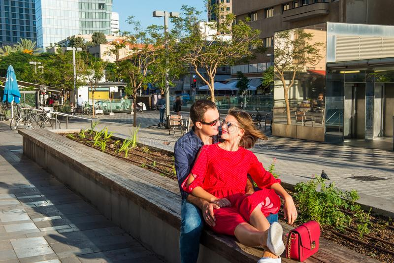 Young loving couple in bright clothes and sunglasse ssitting on the bench in the city area. Embracing, laughing ,relaxing. Happine stock photos