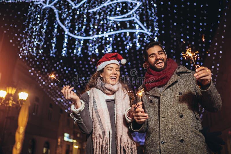 Loving couple burning sparklers by holiday illumination on new years eve royalty free stock images
