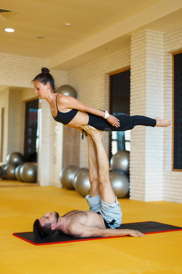 Young loving couple doing yoga in the studio stock images