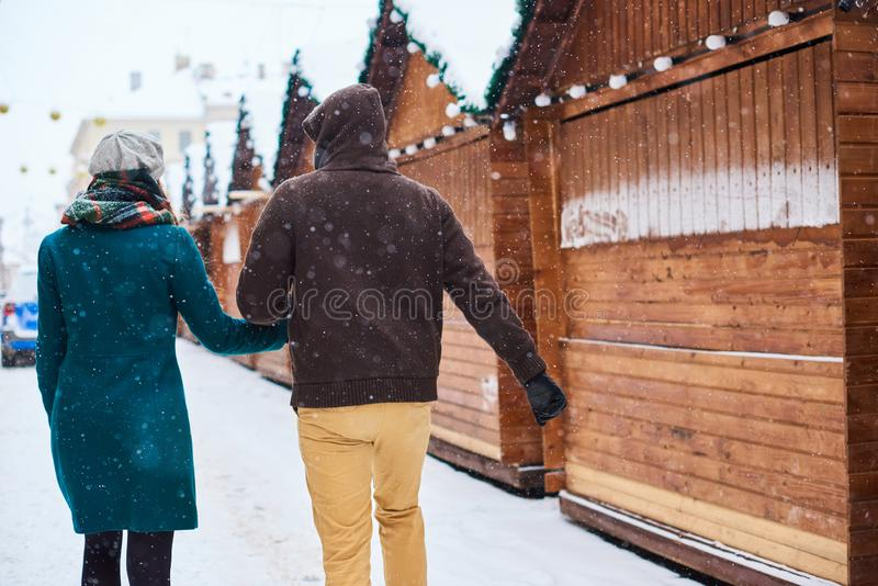 Young loving couple dressed in plaid scarves walk at the old city in winter royalty free stock image