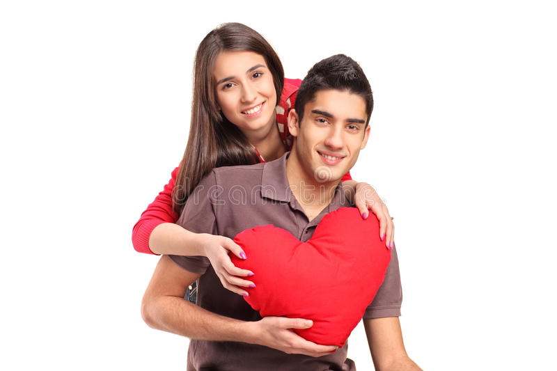 Young loving couple in an embrace. Holding a red heart shaped pillow isolated on white background stock photo