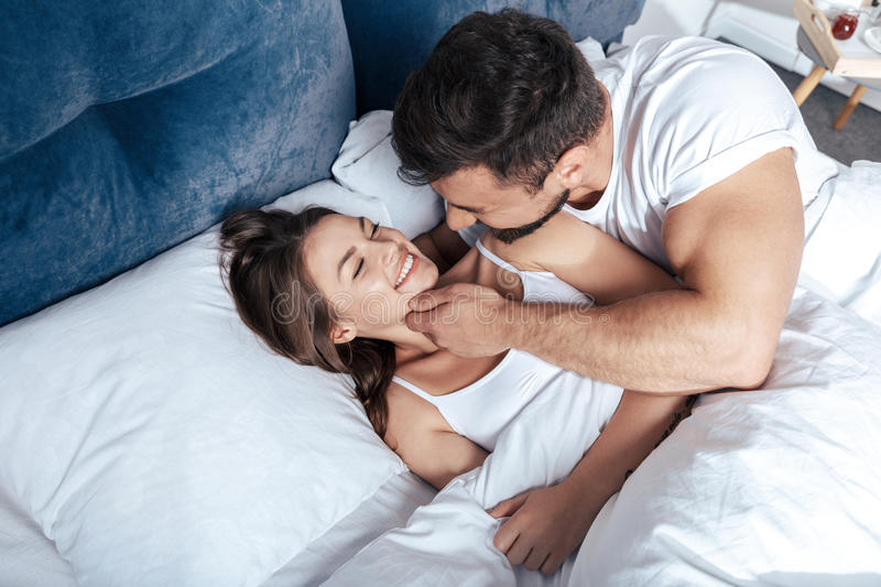 Young loving couple embrace in bed. Portrait of young loving couple embrace in bed stock image