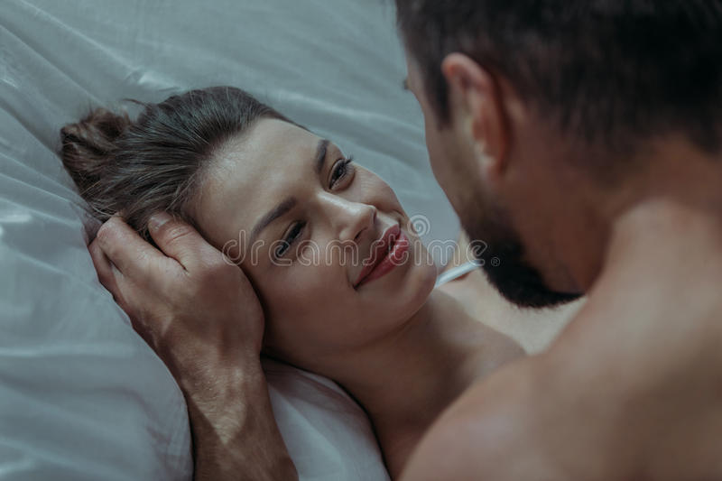 Young loving couple embrace in bed. Portrait of young loving couple embrace in bed royalty free stock photo