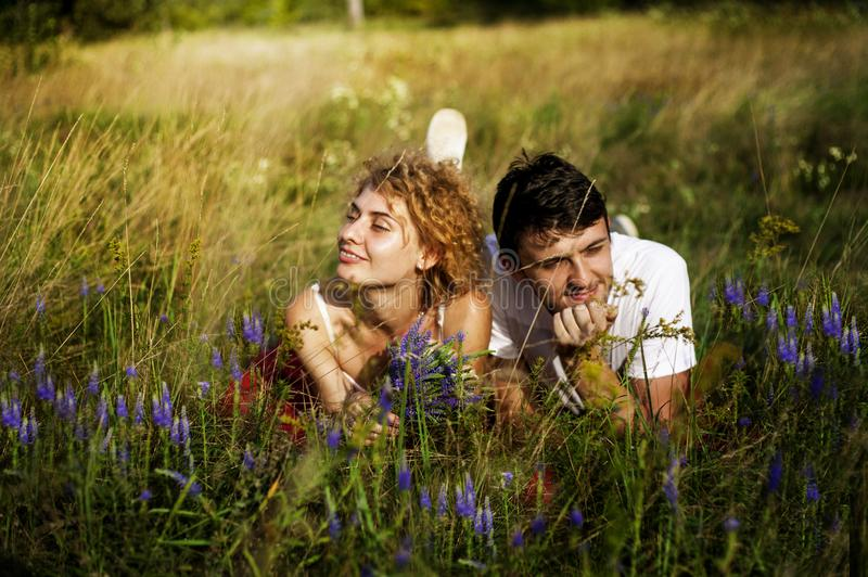 Young loving couple enjoying nature, holding hands and walking on the field with lavender. Beautiful people on nature in spring at stock photos