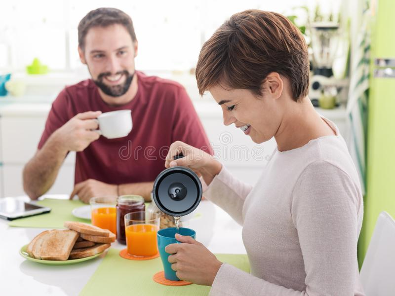 Young loving couple having breakfast at home stock images