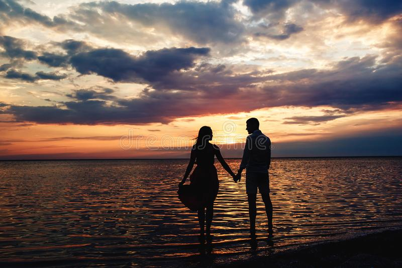 Young loving couple holding hands at sunset on the lake royalty free stock photography