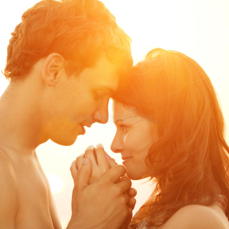A young loving couple hugging and kissing on the beach at suns royalty free stock photos