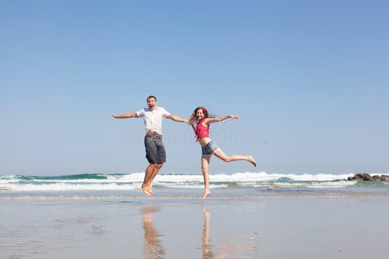 Young loving couple joyfully jumps stock image
