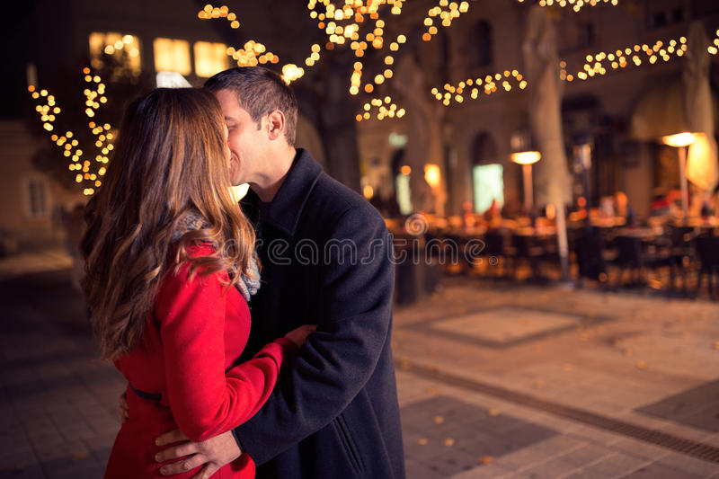Young loving couple kissing in the city center. New Year and Christmas royalty free stock photo