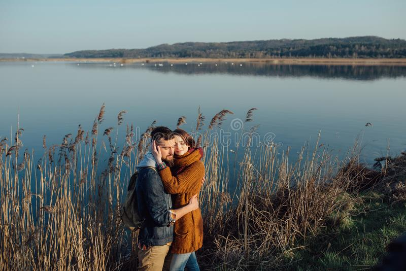 Young loving couple on the lake near the reeds. A young couple in love embraces, and fools around on the shore of the lake near the reeds. feelings, emotions royalty free stock photo