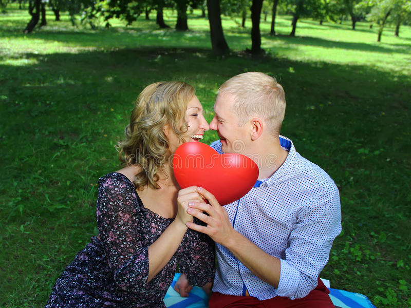 Young loving couple looking at each other and holding a red heart. love story. stock photo