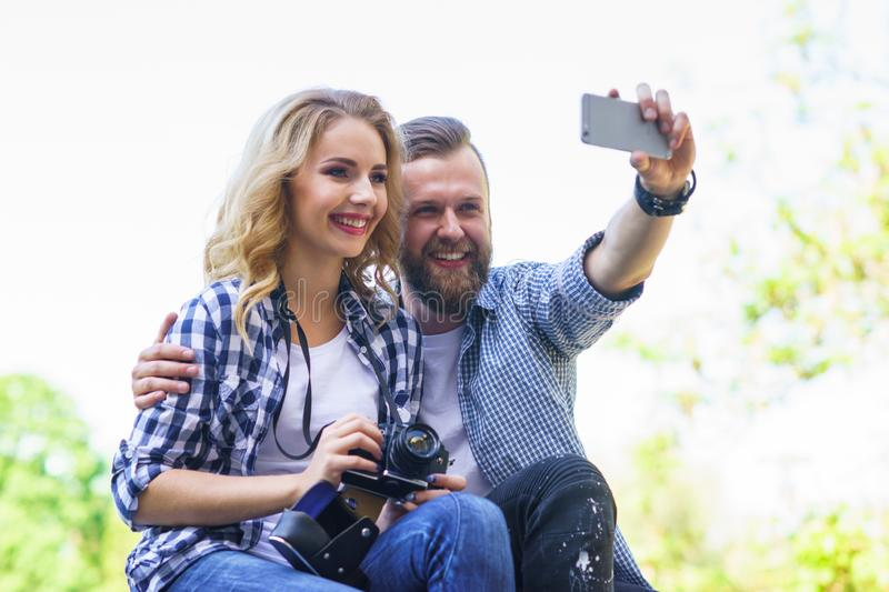 Young loving couple making selfie photo outdoor. royalty free stock image