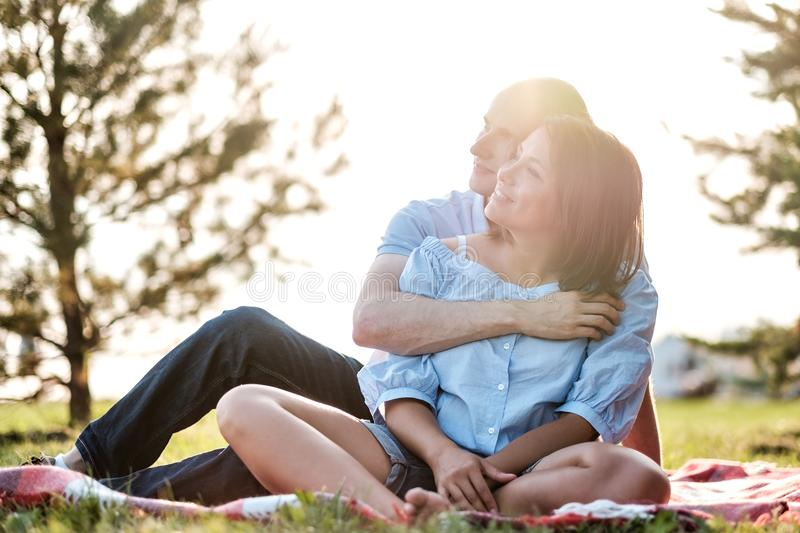 Young loving couple outdoors sitting on grass, hugging and looking away. royalty free stock images